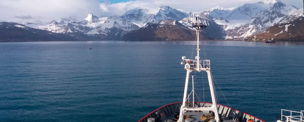 Bow of research ship with ice capped mountains of south giorgia in the background